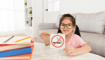 photo of young girl holding a no smoking sign